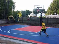 Kid enjoying barely completed navy and red home basketball court in Canton, MA.