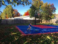 Boy sweeping leaves off navy blue and red backyard basketball court in Canton, MA.