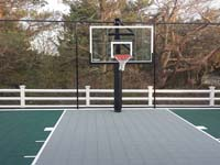 Slate green and titanium backyard basketball court in Plymouth, MA, highlighting fence and goal options.