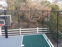 Focus on corner of home basketball court in Plymouth, MAshowing containment fence and hoop, as well as sport surfacec.