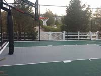 Home basketball court in Plymouth, MA, featuring hoop system, fencing, low impact green and grey outdoor sport tiles.