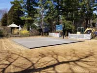 Curing reinforced concrete court foundation for dark green basketball court in Duxbury, MA.