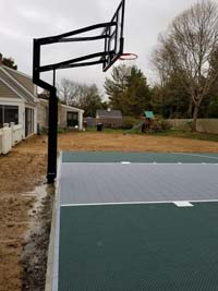 Side view of freshly installed dark green basketball court and hoop, ready for fresh landscaping around it, in Duxbury, MA.