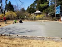 Concrete base construction preceding installation of dark green basketball court in Duxbury, MA.