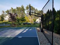 Backyard basketball court featuring a rebounder in Duxbury, MA.