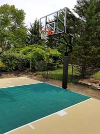 Small sand and green colored basketball court in Easton, MA.