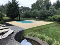 Small backyard basketball in Easton, MA, tiled in sand color, with green key. Shown after landscaping was done and fun is obviously being had by players of all ages.
