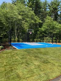 Blue and gray residential basketball court in Easton, MA, new sod lawn in foreground.