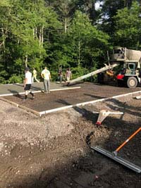 Concrete being pored and smoothed for base of what will become a blue and gray residential basketball court in Easton, MA.