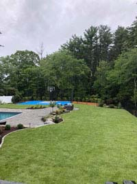 Blue and gray residential basketball court in Easton, MA, shown in distance view with bulk of picture in foreground showing off yard freshly landscaped by Evergreen.