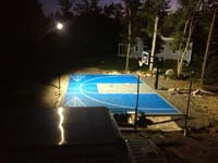 Overview of blue and gray basketball court under optional lighting system at night in Wareham, MA.