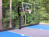 Focus on hoop and rebound fence of blue and grey West Bridgewater basketball court.