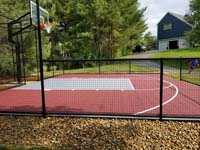 View of kid running to use red and grey home basketball court in Groton, MA.