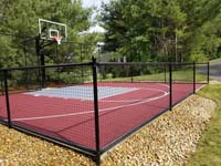 Red basketball court with silver-looking titanium colored key, installed in a side yard in Groton, MA.