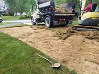 Removal of existing grass before building red and grey home basketball court in Groton, MA. Organic material must be removed, appropriate base material added and compacted, and a reinforced concrete base poured for maximum durability.