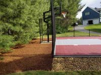 View of red and grey home basketball court in Groton, MA.