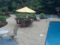 View from a distance of how this green and burgundy multicourt in Kingston, MA fits seemlessly with the pool, hardscapes and beautiful landscape.