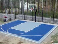 Navy and ice blue backyard basketball court with rebounder and goal system in Kingston, MA.