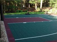 Dark green and burgundy multicourt with basketball goal system and rebounderin Kingston, MA.