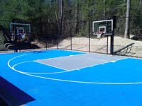 Residential basketball court in Lakeville, MA, made with light blue and ice blue tiles on concrete underlay.