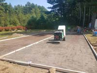 Construction of the base for a basketball court featuring Celtics logo, with fire pit, patio, and light for night play, in Londonderry, NH.