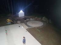 Night preview of incomplete basketball court featuring Celtics logo, with fire pit, patio, and light for night play, in Londonderry, NH.