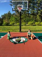 Kids in Celtics uniforms on backyard basketball court with Versacourt custom logo in Londonderry, NH.