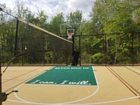 Sand-colored and green basketball court, with optional net for tennis and volleyball, in Londonderry, NH.