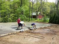 Reinforced concrete is critical to durable construction of a tan and green basketball court in Londonderry, NH.
