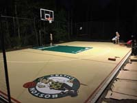 Kids helping to test the lighting adjustments on tan and green basketball court in Londonderry, NH, featuring multiple custom logos and writing, lighting for night play, and optional multicourt net for volleyball.