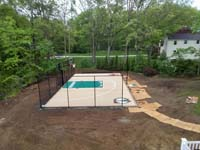 Overview from side, before landscaping, of sand and green backyard basketball court with custiom team logos and text in Londonderry, NH.