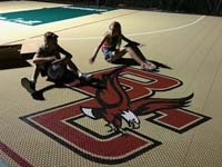 Closeup of kids posing with BC Eagles logo in corner of basketball court.