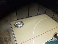 Custom logo under the lights on tan and green basketball court in Londonderry, NH.