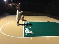 Testing out the night lighting of a tan and green basketball court in Londonderry, NH.