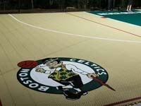 Closeup of custom Celtics logo on corner of sand and green backyard basketball multicourt in Londonderry, NH.