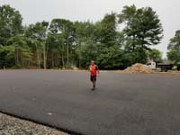 Expanse of pavement to be tiled to create a large royal blue and titanium basketball court with golf seahorse logo at Bay Club in Mattapoisett, MA.