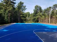 Large commercial royal blue and titanium basketball court with golf seahorse logo at Bay Club in Mattapoisett, MA, as viewed from beneath hoop at one end, looking at the opposite end, showing the sheer size..