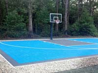 Residential basketball court in light blue and graphite colors, installed in a New England yard much like yours.