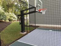 Side view through mesh fence of hoop end of Slate green and titanium silver/grey basketball court in Needham, MA.