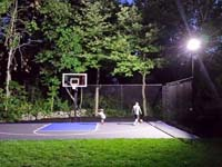 The same back yard corner shown to the right, with a completed residential basketball court shown in use under lights at night in West Bridgewater, MA.