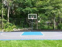 Home basketball court in West Bridgewater, MA, with grey tiles for the primary and blue tiles for the secondary colors.