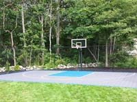 Backyard basketball court with gray and blue sport surface, hoop, fence, and lighting option in West Bridgewater, MA.