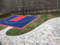 Navy blue and red home basketball court after associated landscape work was completed, located in New England, in Massachusetts, in Bristol County, in North Attleboro.