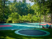 In-ground trampoline in foreground, installed along with construction of this large backyard multicourt, combining basketball, lines for secondary games, and an adjustable net for tennis or volleyball, located in Pembroke, MA.