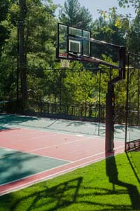 Backyard basketball court with net for tennis or volleyball, fresh sod, in-ground trampoline in Pembroke, MA.