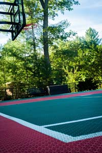 Fairly close look at the red and green tile colors at one end of a backyard basketball court with multicourt net for tennis or volleyball, adjacent in-ground trampoline, and lighting system in Pembroke, MA.