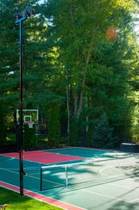 Large home basketball court with net for tennis or volleyball, in-ground trampolin, and lighting system in Pembroke, MA.