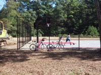 Freshly replaced public basketball court in Plympton, MA with graphite and red Versacourt tiles, plus rebound fencing and goal system.