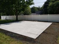 Concrete foundation ready for small slate green and titanium residential basketball court in Reading, MA.