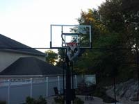Backyard basketball court hoop adjustment in Stoneham, MA.